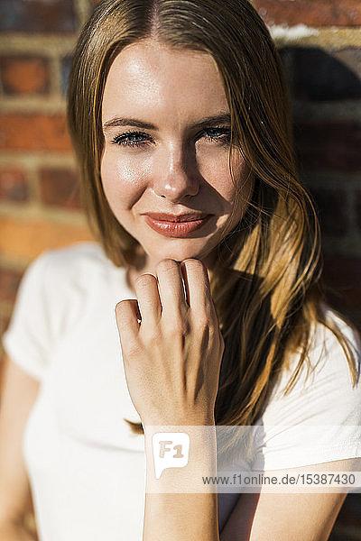 Junge Frau vor Backsteinmauer  Porträt