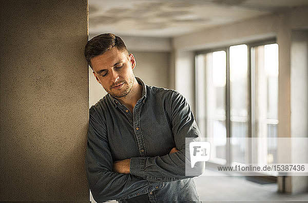 Exhausted businessman leaning on wall  with arms crossed
