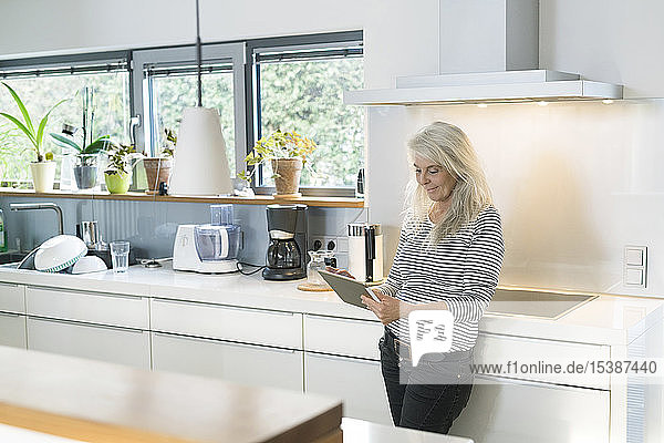 Content woman standing in kitchen using digital tablet