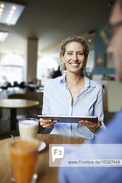 Smiling woman and man with tablet in a cafe