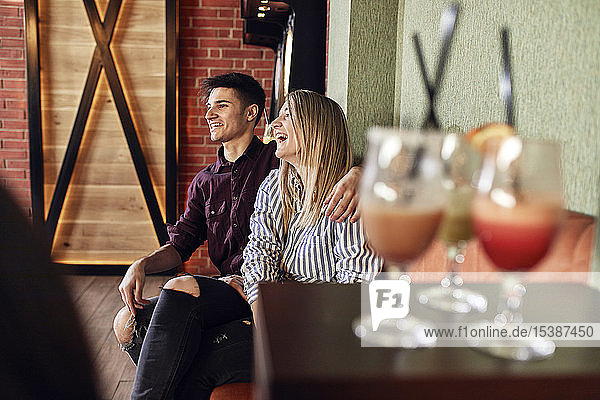 Happy couple sitting in a bar