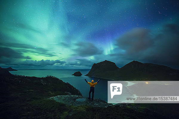 Norway  Lofoten Islands  Haukland Beach  northern lights  man with raised arms