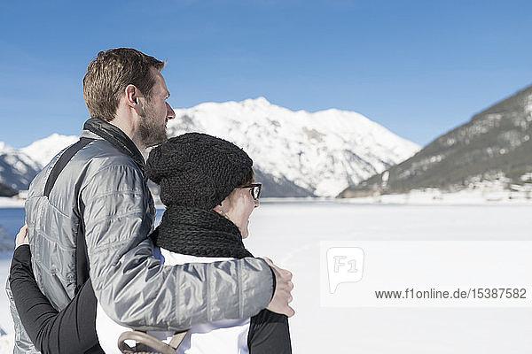 Österreich  Tirol  Achensee  Paar mit Blick auf den zugefrorenen See im Winter