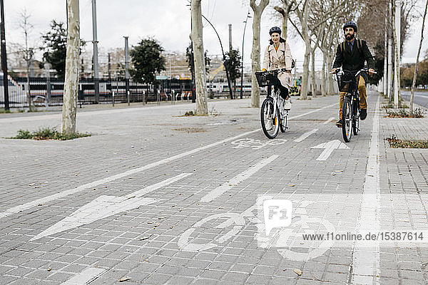 Couple riding e-bikes in the city on bicycle lane