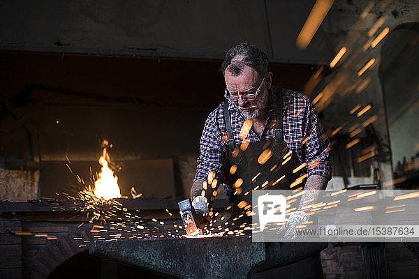 Schmied  der in seiner Werkstatt mit dem Hammer am Amboss arbeitet