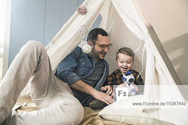 Happy father and son playing with a robot in tent at home