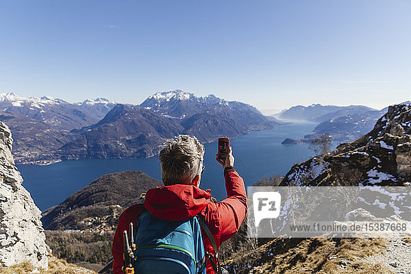 Italy  Como  man on a hiking trip in the mountains above Lake Como taking photo with cell phone