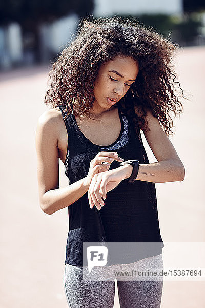 Sporty young woman looking at her smartwatch outdoors