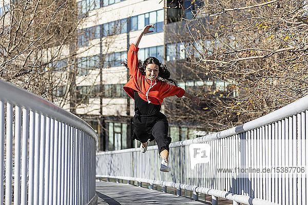 Junge zeitgenössische Tänzerin auf einer Fußgängerbrücke