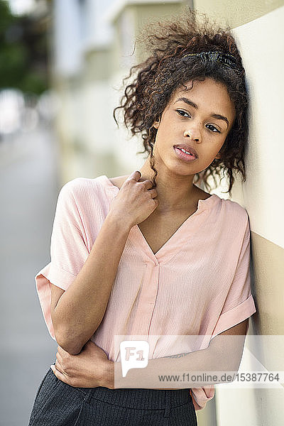 Serious young woman leaning against a wall looking around
