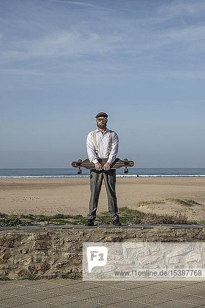 Mann mit Longboard steht auf einer Mauer vor Strand und Meer