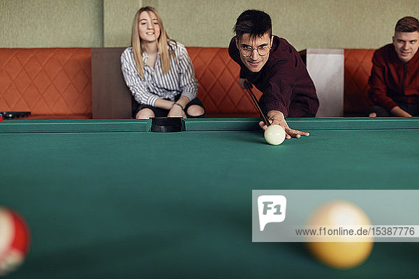 Man playing billiards watched by friends