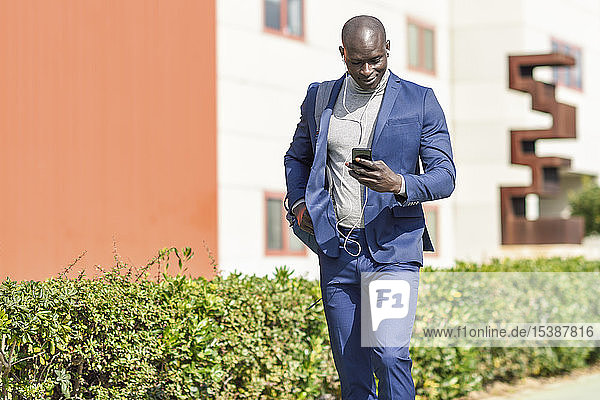 Businessman wearing blue suit listening music with earphones and smartphone