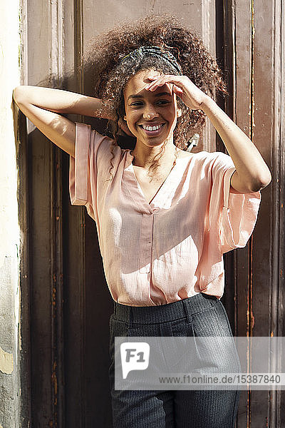 Lächelnde junge Frau  die sich im Freien gegen eine Wand stellt