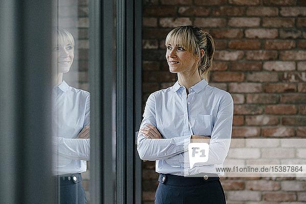 Zuversichtliche Geschäftsfrau schaut mit verschränkten Armen aus dem Fenster
