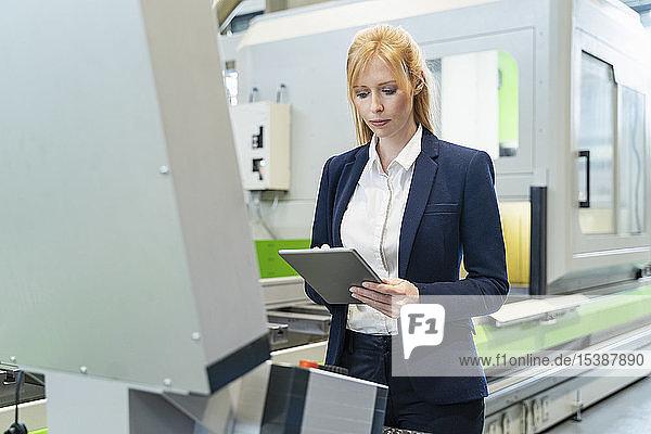 Geschäftsfrau benutzt Tablette an Maschine in Fabrik