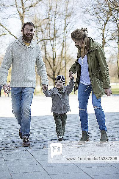 Glückliche Eltern gehen Hand in Hand mit ihrem Sohn