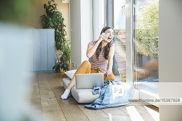 Laughing young woman sitting at the window at home using cell phone and laptop