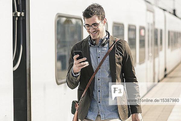 Lächelnder junger Mann mit Handy am Bahnsteig