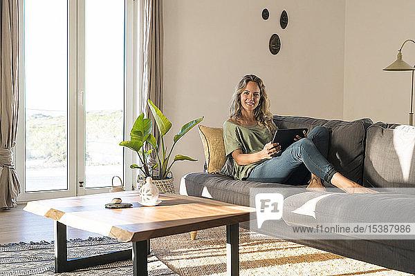 Porträt einer lächelnden Frau  die sich zu Hause auf der Couch mit Tablette vergnügt
