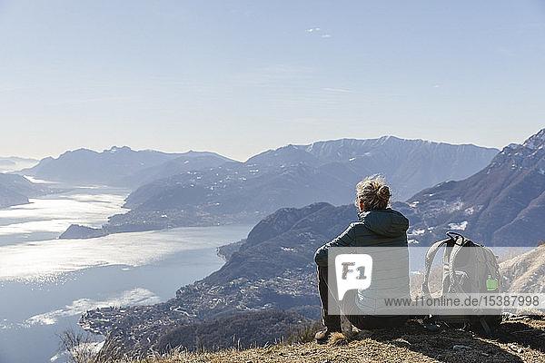 Italien  Como  Lecco  Frau auf einer Wanderung in den Bergen über dem Comer See sitzend und geniesst die Aussicht
