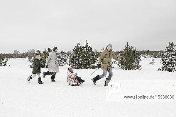 Familie amüsiert sich mit Schlitten in schneebedeckter Landschaft