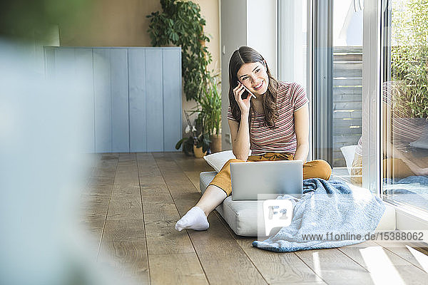 Smiling young woman sitting at the window at home using cell phone and laptop