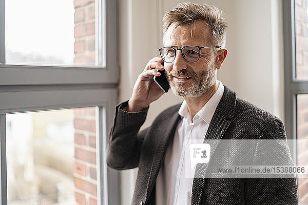 Businessman on cell phone at the window in office