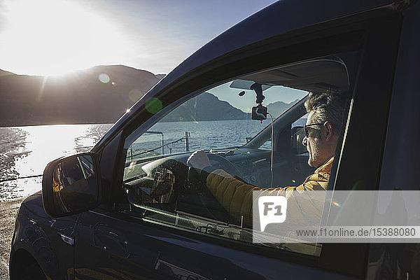 Italien  Como  Mann sitzt im Auto  während er mit der Fähre den See überquert