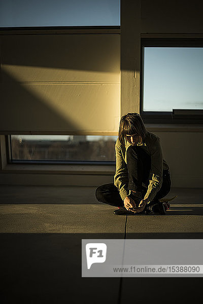Businesswoman sitting on office floor at sunset  using smartphone