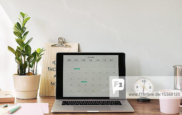 Geöffneter Laptop mit einem Kalender auf dem Schreibtisch im Heimbüro