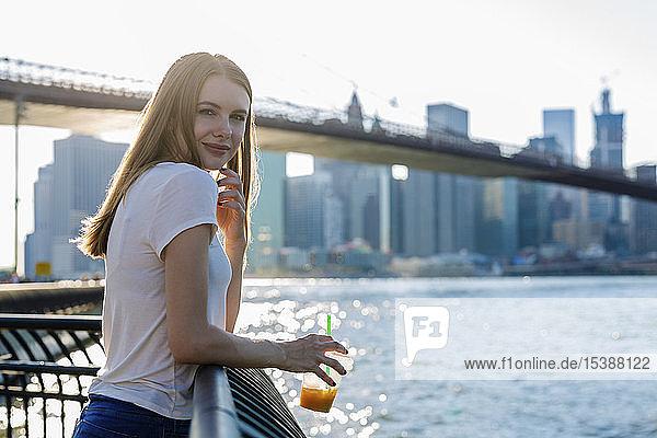 Junge Frau erkundet New York City mit Blick auf die Brooklyn Bridge