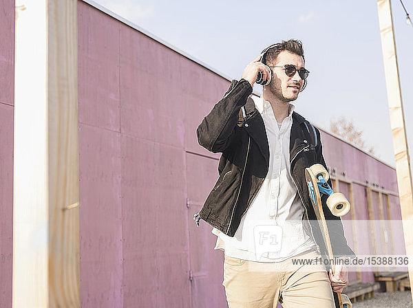 Young man with skatebaord and headphones on the move in the city