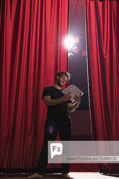 Barfüssiger Schauspieler steht auf der Bühne des Theaters und liest Skript Barfüssiger Schauspieler steht auf der Bühne des Theaters und liest Skript