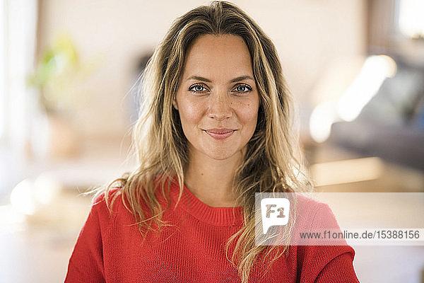 Porträt einer lächelnden blonden Frau zu Hause