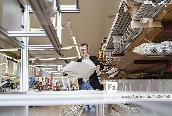 Geschäftsmann mit Plan im Fabriklager