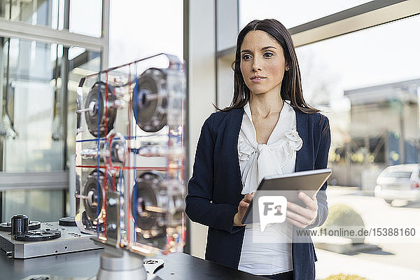 Geschäftsfrau mit Tablette betrachtet Maschine in einer modernen Fabrik