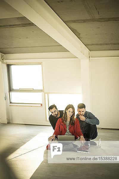 Kollegen sitzen auf dem Boden leerer Büroräume  machen Pläne  benutzen Laptops