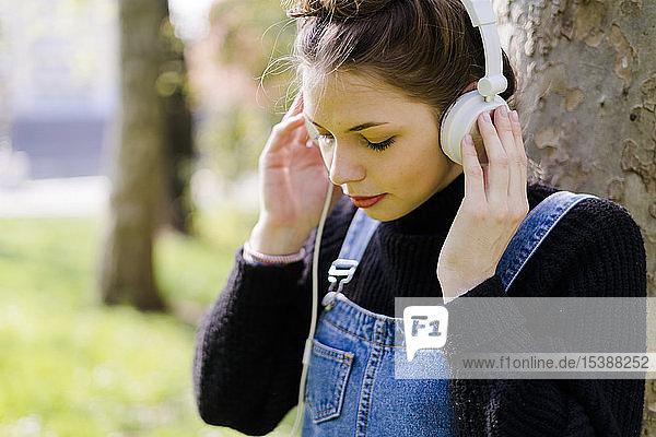 Junge Frau mit Kopfhörern in einem Park