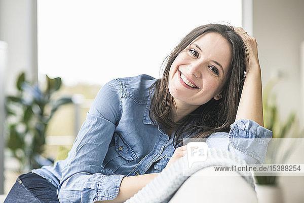 Porträt einer glücklichen Frau  die zu Hause auf der Couch sitzt