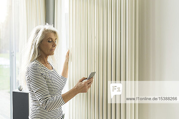 Mature woman with smartphone checking heating in living room of smart home