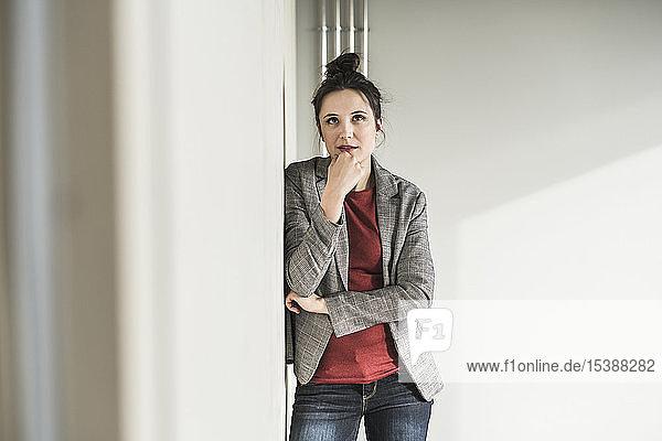 Porträt einer Geschäftsfrau  die im Büro gegen eine Wand lehnt und denkt