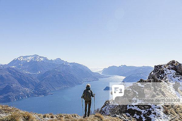 Italien  Como  Lecco  Frau auf einer Wanderung in den Bergen über dem Comer See  die die Aussicht genießt