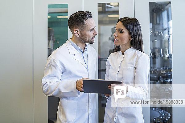 Kollegen mit Tablette tragen Laborkittel in moderner Fabrik