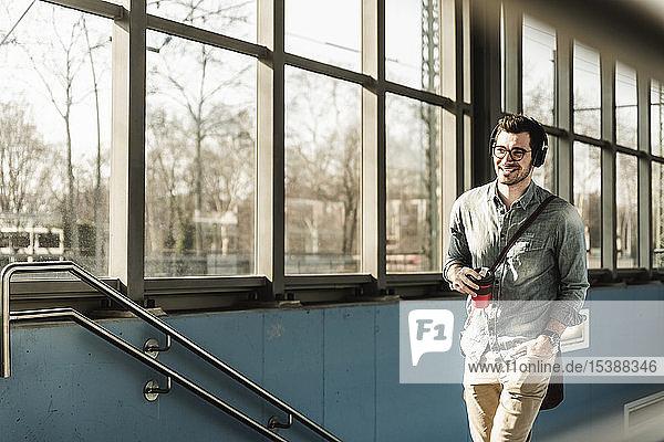 Lächelnder junger Mann mit Kopfhörern und Kaffee zum Mitnehmen auf dem Bahnhof