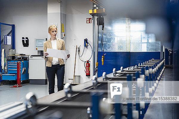 Geschäftsfrau mit Plan schaut sich Maschine in Fabrik an