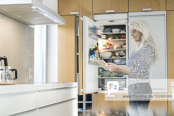 Content mature woman standing in kitchen at smart home checking fridge with digital tablet