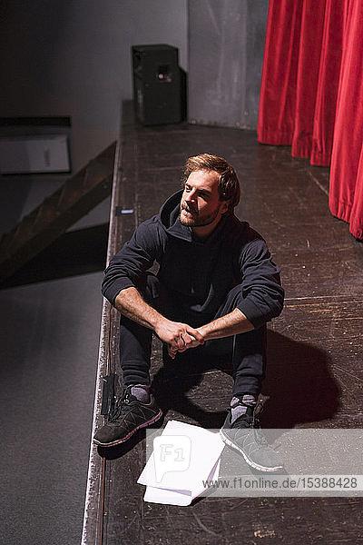 Probender Schauspieler sitzt mit Drehbuch auf der Theaterbühne Probender Schauspieler sitzt mit Drehbuch auf der Theaterbühne