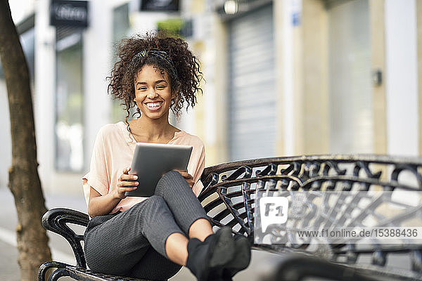 Portrait of happy young woman sitting on a bench using tablet