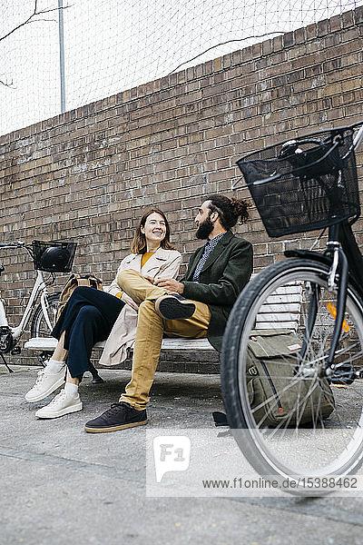 Ehepaar sitzt auf einer Bank neben E-Bikes und unterhält sich